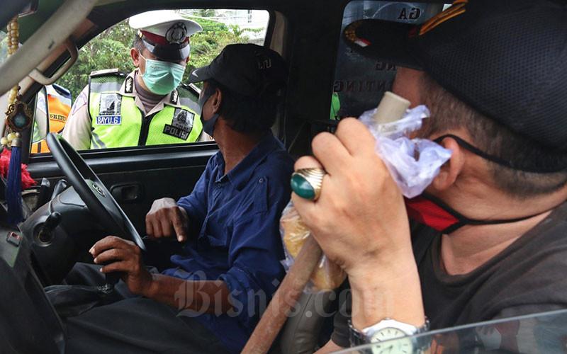 Petugas gabungan melaksanakan pengawasan dalam Penerapan Sosial Berskala Besar (PSBB) di Jalan Ciledug Raya, Jakarta, Jumat (10/4/2020). Kegiatan pelaksanaan pengawasan PSBB itu dilakukan untuk mengingatkan kewajiban warga untuk memakai masker dan aturan penumpang dalam satu kendaraan. Bisnis - Eusebio Chrysnamurti
