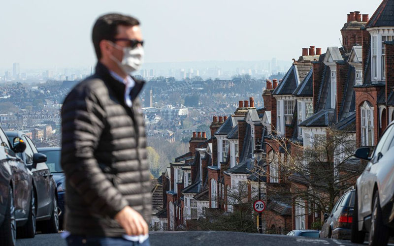 Seorang lelaki menyeberangi sebuah jalan di London, Inggris, berlatar belakang deretan properti residensial./Bloomberg - Hollie Adams