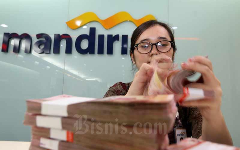 Karyawati menghitung uang pecahan uang Rp100.000 di salah satu kantor cabang milik PT Bank Mandiri Tbk di Jakarta, Rabu (12/6/2019). Bisnis - Nurul Hidayat