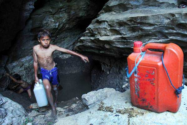 Seorang anak mengambil air dari dalam gua kars Rammang-rammang, Desa Salenrang, Kabupaten Maros, Sulawesi Selatan, Sabtu (16/9). - ANTARA/Abriawan Abhe