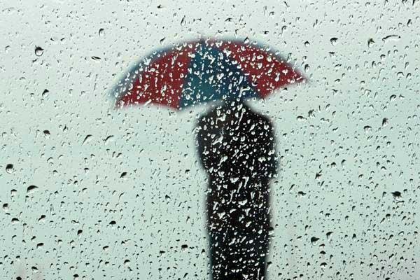 Seorang pria membawa payung saat hujan di Kolombo, Sri Lanka, Jumat (01/12). - Reuters/Dinuka Liyanawatte