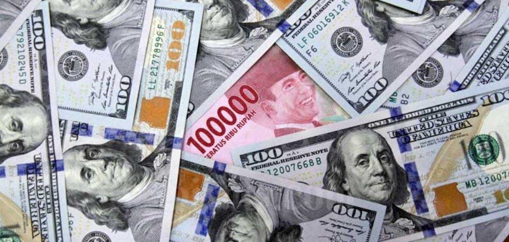 Karyawati menunjukan uang Rupiah dan dolar AS di salah satu gerai penukaran mata uang asing di Jakarta, Minggu (7/6/2020). - Bisnis/Arief Hermawan P