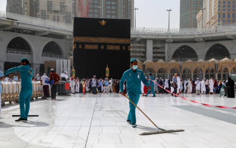 Petugas memakai masker wajah pelindung saat mereka membersihkan lantai di Masjidil Haram di kota suci Mekah, Arab Saudi, 3 Maret 2020. REUTERS n