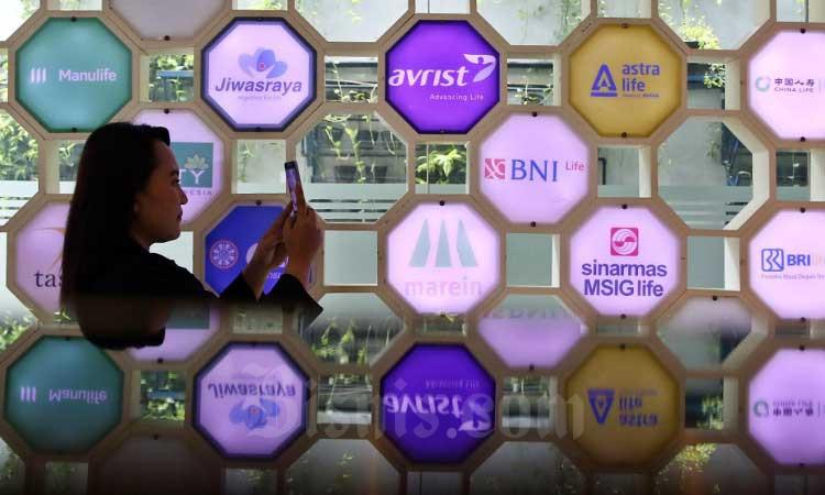 Karyawan melihat logo-logo perusahaan asuransi yang berada di Kantor Asosiasi Asuransi Jiwa Indonesia (AAJI) di Jakarta, Senin (2/3/2020). Bisnis - Eusebio Chrysnamurti