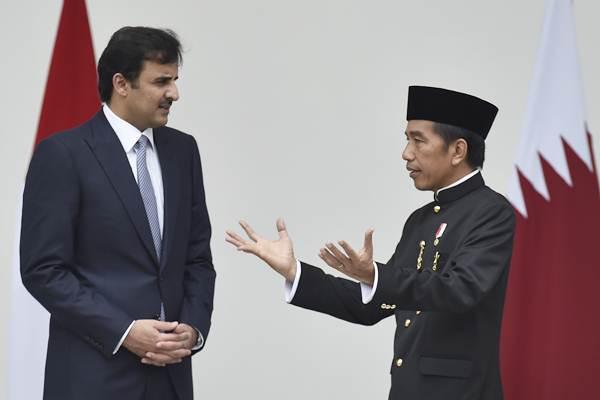 Presiden Joko Widodo (kanan) berbincang dengan Emir Qatar Sheikh Tamim bin Hamad Al Thani saat kunjungan kenegaraan di beranda belakang Istana Bogor, Jawa Barat, Rabu (18/10). - ANTARA/Puspa Perwitasari
