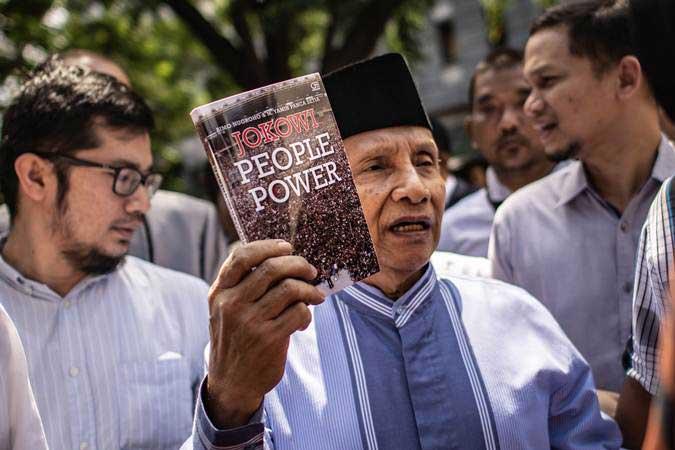 Amien Rais (tengah) menunjukkan buku berjudul Jokowi People Power saat jeda pemeriksaan untuk salat Jumat di Direktorat Reserse Kriminal Umum (Ditreskrimum) Polda Metro Jaya, Jakarta, Jumat (24/5/2019). - ANTARA/Aprillio Akbar