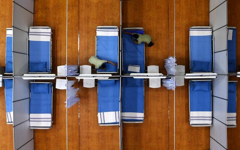 Pekerja merapikan tempat tidur di Sarana Olaraga Tri Dharma yang dijadikan ruang isolasi mandiri Covid-19 di Gresik, Jawa Timur, Senin (20/7/2020). Petrokimia Gresik mengubah sarana olaraga tersebut menjadi ruang isolasi mandiri Covid-19 yang terdiri dari 40 ruangan dengan kapasitas 80 tempat tidur yang telah dilengkapi sejumlah fasilitas pendukung, hal itu bertujuan sebagai bentuk antisipasi tingginya kasus mewabahnya virus Corona di Surabaya Raya. - Antara/Zabur Karuru