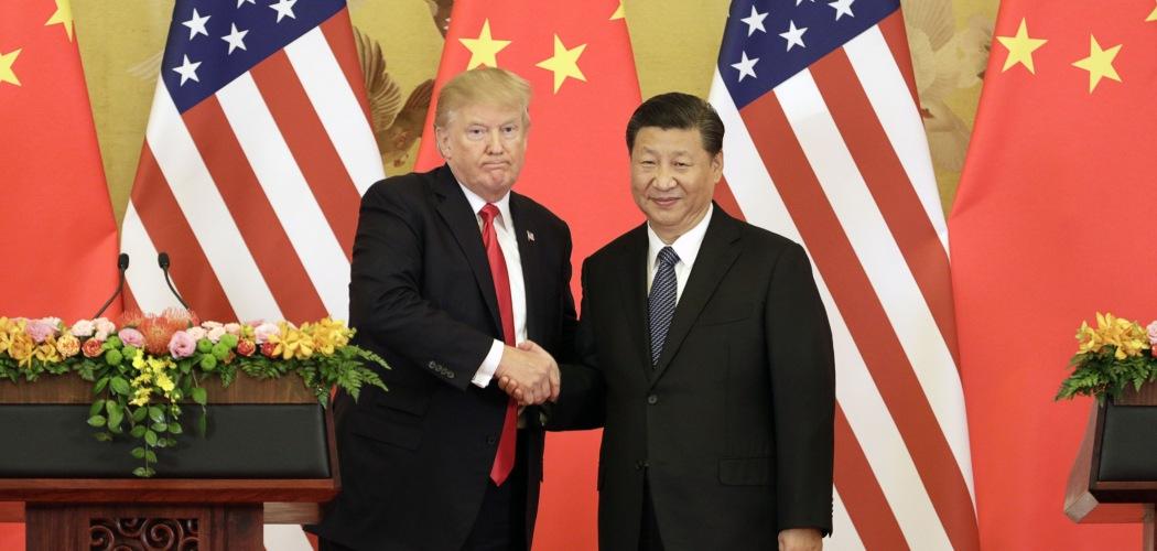 Presiden AS Donald Trump dan Presiden China Xi Jinping bersalaman dalam konferensi pers di Great Hall of the People di Beijing, China, Kamis (9/11/2017). - Bloomberg/Qilai Shen