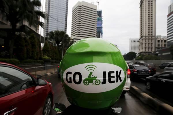 Pengemudi Gojek melintas di kawasan bisnis di Jakarta. - Reuters