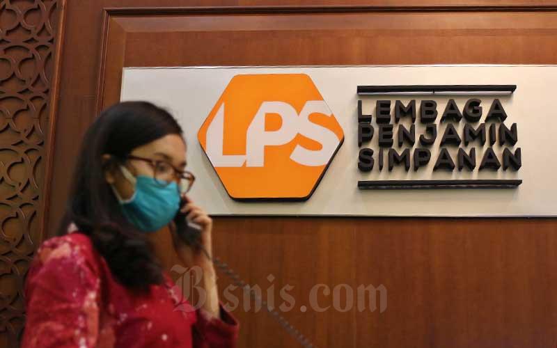 Karyawan beraktivitas di dekat logo Lembaga Penjamin Simpanan (LPS) di Jakarta, Jumat (10/7/2020). Bisnis - Eusebio Chrysnamurti
