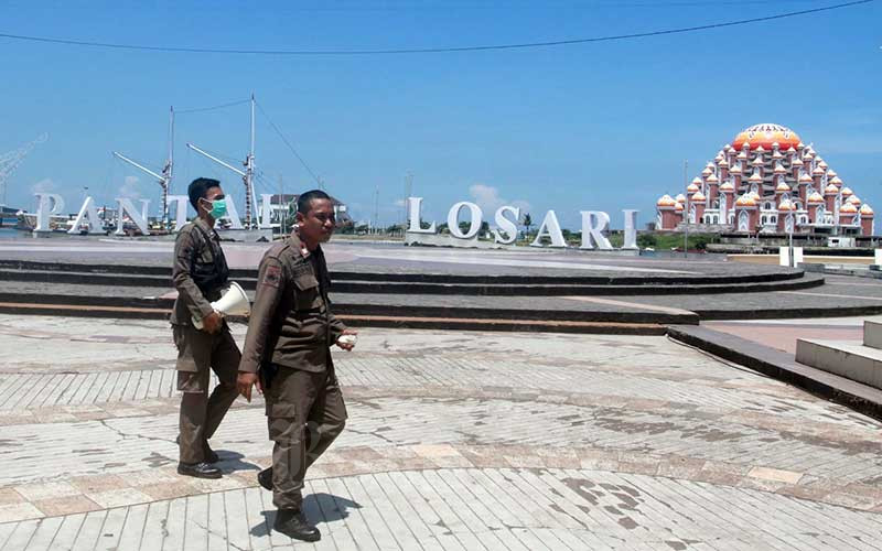 Petugas berpatroli dan mengosongkan area anjungan Pantai Losari Makassar, Kamis (19/3/2020). Pemerintah Kota Makassar menutup anjungan Pantai Losari Makassar hingga 31 Maret guna mencegah kerumunan massa yang berpotensi penyebaran virus Covid 19. Bisnis - Paulus Tandi Bone