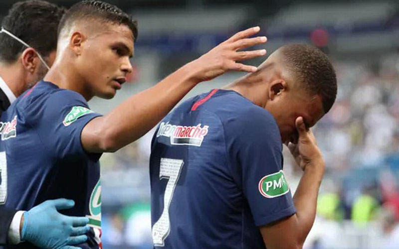 Penyerang PSG Kylian Mbappe (kanan) menahan sakit dan dihibur kapten tim Thiago Silva setelah dihajar pemain belakang Saint-Etienne Loic Perrin. - The Guardian