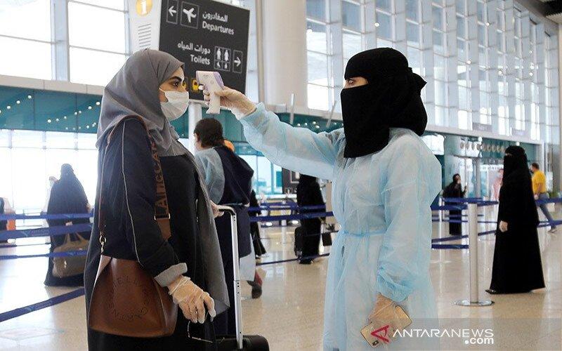 Seorang petugas keamanan wanita memeriksa suhu pengunjung wanita di Bandara Internasional Riyadh, Arab Saudi, (31/5/2020). Pemerintah Arab Saudi melakukan pelonggaran terbatas dan membuka kembali penerbangan domestik setelah wabah vorus corona (COVID-19). ANTARA/REUTERS/Ahmed Yosri - aa.