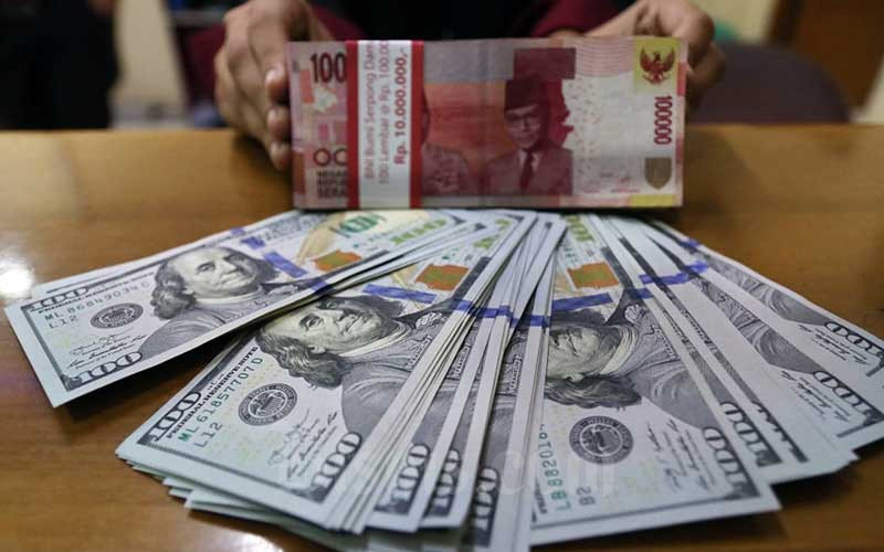 Karyawan menunjukan uang dolar Amerika Serikat (AS) dan Rupiah di salah satu gerai penukaran mata uang asing di Jakarta, Rabu (22/7/2020). Bisnis - Eusebio Chrysnamurti