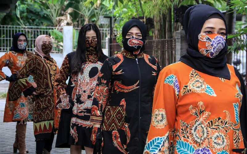 Sejumlah model mengenakan busana perpaduan batik dan tenun di rumah busana kawasan Candi, Sidoarjo, Jawa Timur, Rabu (15/7/2020). Peragaan busana dengan menerapkan protokol kesehatan tersebut bertujuan untuk adaptasi dengan tatanan normal baru dan inspirasi bagi industri kreatif di Indonesia di tengah pandemi Covid-19. - Antara/Umarul Faruq