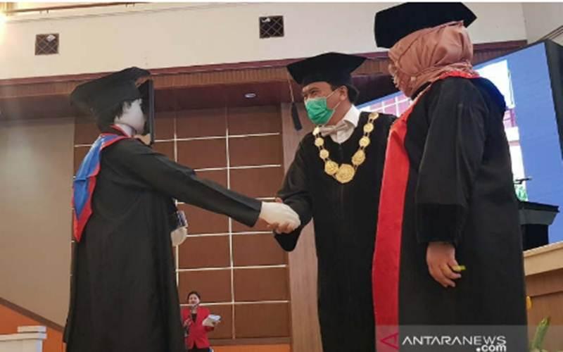 Rektor Undip Yos Johan menyalami robot yang mewakili lulusan Undip dalam acara wisuda di Semarang, Senin (27/7/2020). - ANTARA/I.C.Senjaya