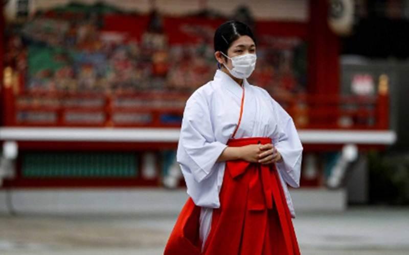 Seorang Shinto menggunakan masker wajah saat berada di sebuah kuil di tengah merebaknya Covid-19 di Tokyo, Jepang, Rabu (15/7/2020)./ANTARA - REUTERS/Issei Kato