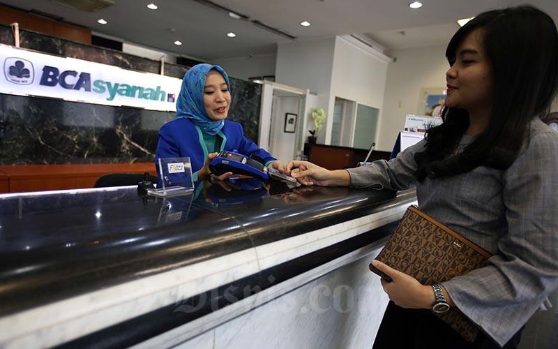 Karyawan melayani nasabah yang melakukan transaksi di kantor cabang Bank BCA Syariah di Jakarta, Selasa (7/1/2020). Bisnis - Abdullah Azzam