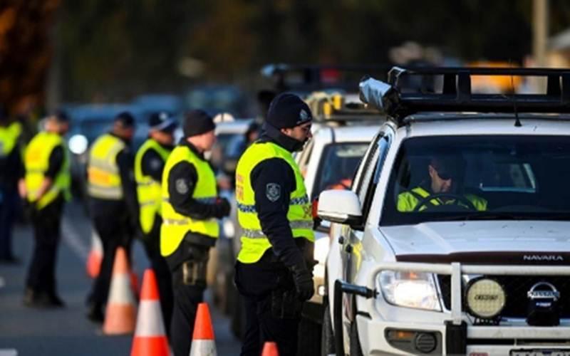 Petugas kepolisian NSW berbicara kepada pengemudi yang akan menyeberang dari Negara Bagian Victoria ke New South Wales (NSW) di pos pemeriksaan perbatasan, yang ditutup karena lonjakan kasus penyakit virus Corona (COVID-19), di Albury, New South Wales, Australia, Rabu (8/7/2020)./ANTARA - AAP Image/Lukas Coch via REUTERS