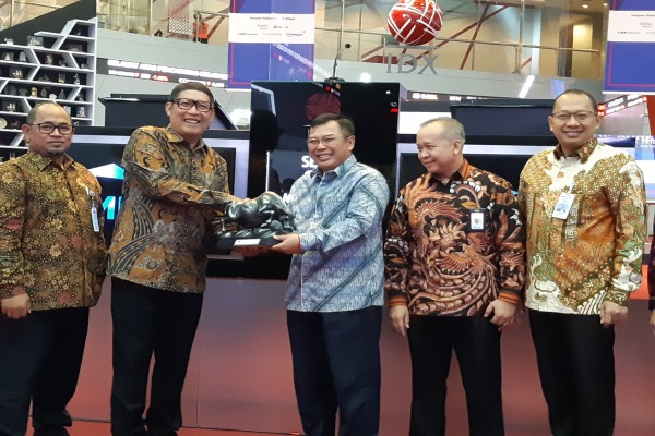 Direktur Utama Bursa Efek Indonesia Inarno Djayadi (kedua dari kiri) memberikan cindera mata kepada Direktur Utama SMF Anata Wiyogo usai pencatatan Penawaran Umum Obligasi Berkelanjutan IV SMF Tahap VIII Tahun 2019, di Gedung Bursa Efek Indonesia, pada Senin (25/3/2019)./Bisnis - Emanuel B.  Caesario