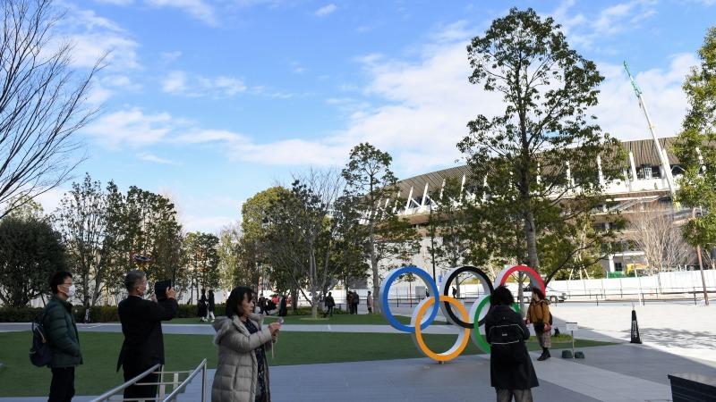 Warga berfoto di depan logo Olimpiade di dekat New National Stadium, yang berperan sebagai venue utama untuk Olimpiade Tokyo 2020 dan Paralympic 2020, di Tokyo, Jepang, Rabu (19/2/2020)./Bloomberg - Noriko Hayashi
