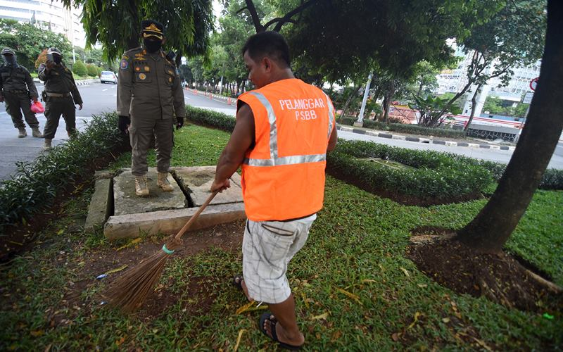 Seorang warga membersihkan sampah setelah dijatuhi hukuman sosial karena tidak mengenakan masker saat terjaring razia penindakan pelanggaran aturan Pembatasan Sosial Berskala Besar (PSBB) oleh Satpol PP di kawasan Kuningan, Jakarta, Jumat (15/5/2020). - ANTARA/Indrianto Eko Suwarso