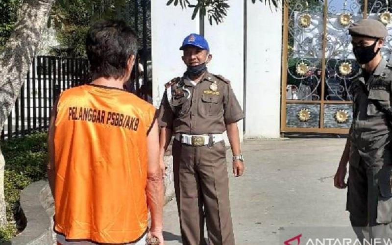 Satpol PP Cianjur, Jawa Barat, mengawasi seorang warga yang dijatuhi sanksi sosial karena tidak mengunakan masker saat beraktivitas di luar rumah dengan cara mengunakan rompi oranye membersihkan alun-alun Cianjur dari sampah. - Antara