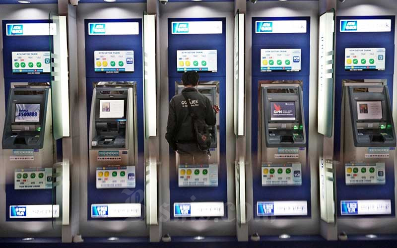 Nasabah melakukan transaksi lewat mesin anjungan tunai mandiri (ATM) di Tangerang Selatan, Banten, Sabtu (28/3/2020). Bisnis - Eusebio Chrysnamurti