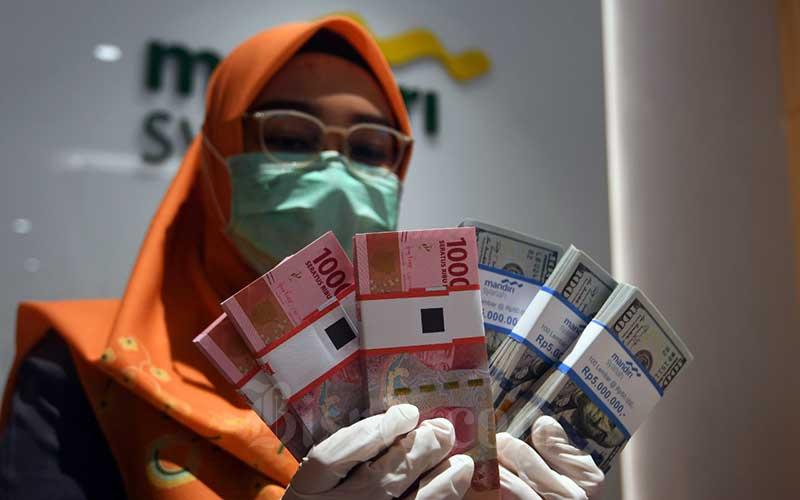 Pegawai bank menata uang dolar di kantor cabang bank Mandiri Syariah di Jakarta, Senin (20/4/2020). Bisnis - Abdurachman