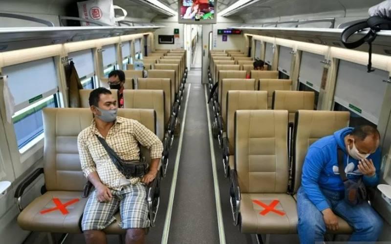 Sejumlah penumpang dengan mengenakan masker di dalam gerbong kereta api luar biasa relasi Gambir-Surabaya Pasar Turi lintas selatan di Stasiun Gambir, Jakarta. - Antara