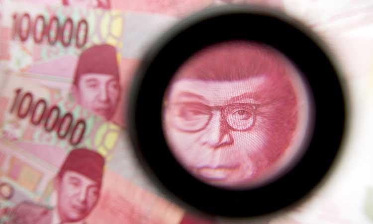 Gambar mantan Wakil Presiden Mohammad Hatta pada uang kertas Indonesia 100.000 rupiah terlihat melalui kaca pembesar di Bangkok, Thailand, (15/09/2015). Blommberg - Brent Lewin