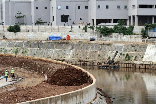 Pekerja melintas di area pembangunan turap bantaran Sungai Ciliwung, di kawasan Kampung Melayu, Jakarta, Rabu (22/3). - Antara/Risky Andrianto