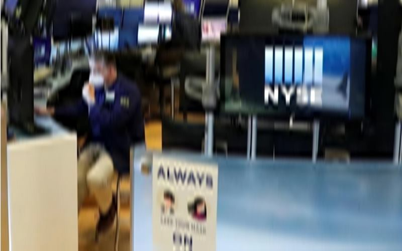 Seorang pedagang menyesuaikan maskernya saat ia bekerja di lantai New York Stock Exchange ketika wabah Virus Corona berlanjut di wilayah Manhattan di New York, AS, 28 Mei 2020. - Antara/Reuters