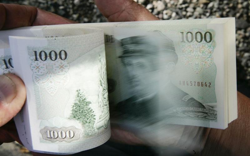 Seorang kasir valas menunjukkan uang pecahan 1.000 peso di Santiago, Chile