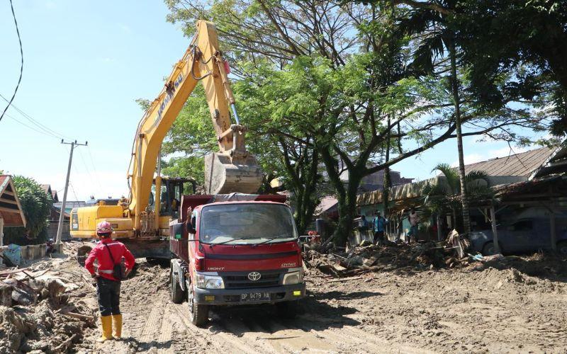 Tim dari PT Brantas Abipraya melakukan proses pembersihan Jalan Salawati Daud, Kecamatan Masamba, Kabupaten Luwu Utara, Sulawesi Selatan yang masih tertutup material kayu dan lumpur (19/7/2020). - Dok. BNPB