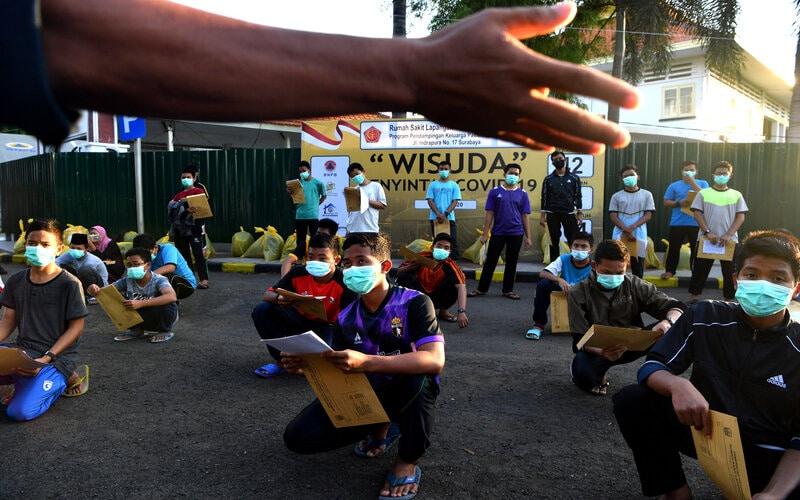 Sejumlah santri asal Ponpes Gontor mendengarkan penjelasan petugas ketika mengikuti wisuda penyintas COVID-19 di halaman Rumah Sakit Lapangan Surabaya, Jawa Timur, Selasa (28/7/2020). Berdasarkan data Satgas penanganan Covid-19 menyatakan jumlah pasien sembuh di Jawa Timur pada (28/7) sebanyak 401 pasien sehingga total pasien yang dinyatakan sembuh tercatat 13.081 orang. - Antara/Zabur Karuru