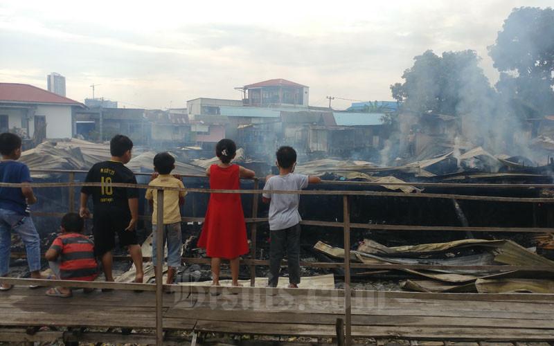 Anak-anak tengah melihat puing rumah warga yang dilalap api pada Kamis dini hari 30 Juli 2020. Sebanyak 35 orang kehilangan tempat tinggal akibat kejadian ini.  - Bisnis/Bobi Bani