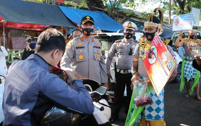 Anggota kepolisian turun langsung ke jalan untuk menyampaikan penggunaan masker pelindung. - Bisnis/Hakim Baihaqi