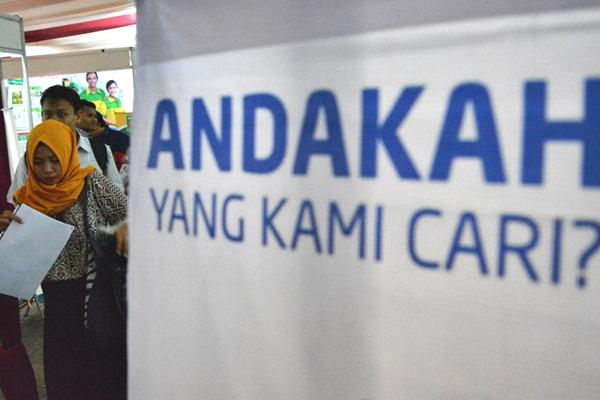 Pencari kerja melintas di dekat stan sebuah perusahaan pada bursa kerja di Disnakertrans Kota Semarang, Jawa Tengah, Rabu (19/4). - Antara/R Rekotomo