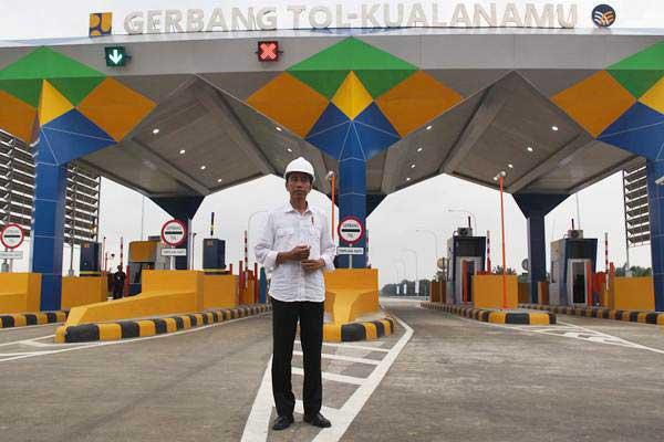 Presiden Joko Widodo berdiri di depan gerbang jalan tol Kualanamu ketika meninjau jalan tol Trans Sumatra di sela-sela peresmiannya, di Deli Serdang, Sumatra Utara, Jumat (13/10). Presiden Joko Widodo meresmikan jalan tol Trans Sumatera ruas Medan-Kualanamu-Tebing Tinggi sepanjang 61,72 km dan Medan-Binjai sepanjang 10,6 km yang telah siap dioperasikan. - ANTARA/Septianda Perdana