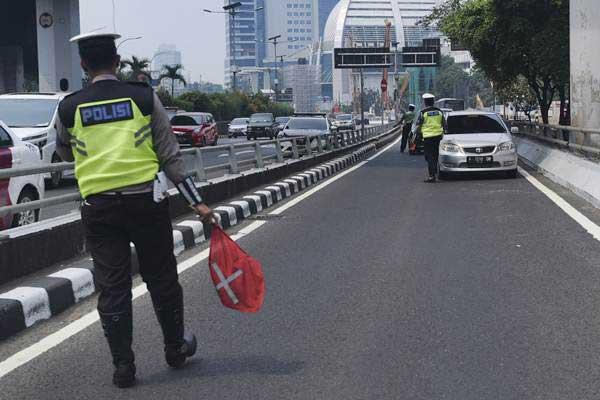 Petugas Ditlantas Polda Metro Jaya memberhentikan mobil berpelat nomor genap yang memasuki Jalan Gatot Soebroto, Jakarta, Rabu (1/8/2018). - ANTARA/Hafidz Mubarak A