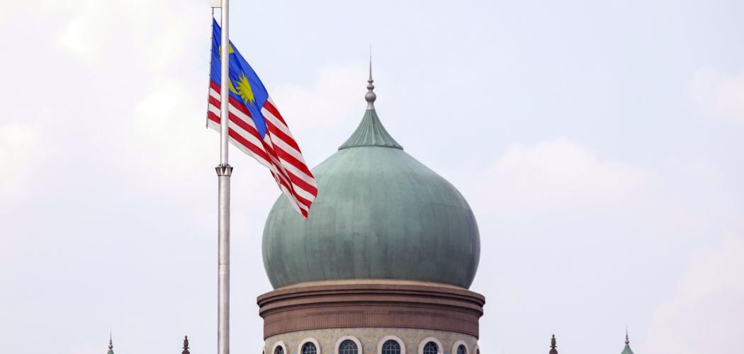 Bendera Malaysia berkibar di depan Kantor Perdana Menteri (PM) Malaysia di Putrajaya, Malaysia, Senin (9/3/2020). - Bloomberg/Joshua Paul