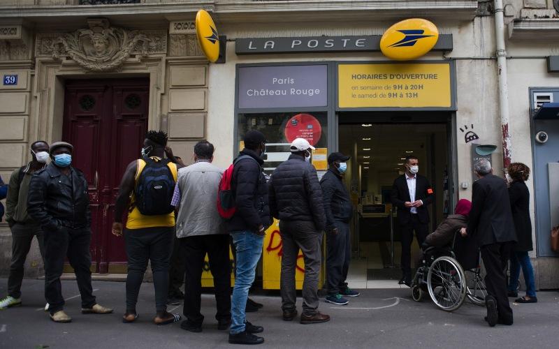 Nasabah mengantre di luar salah satu cabang La Banque Postal SA di Paris, Prancis, Selasa (9/6/2020). - Bloomberg/Nathan Laine\n