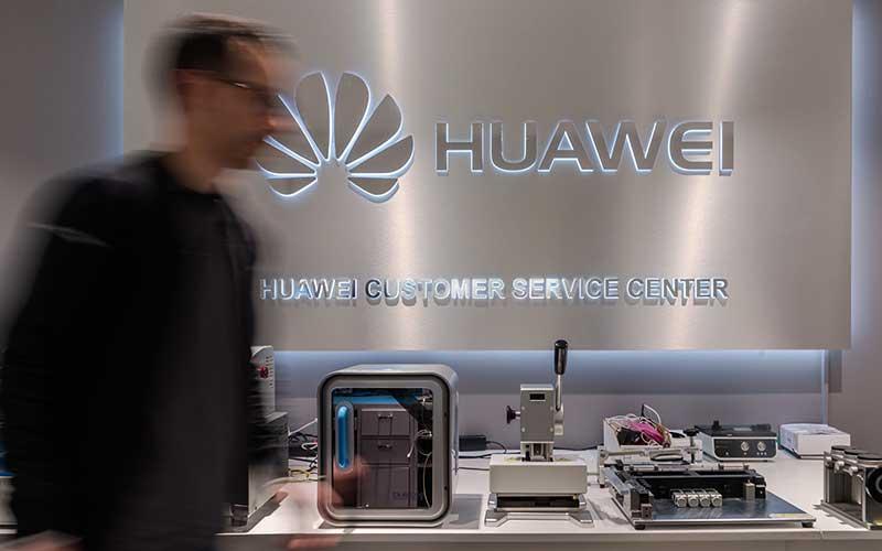 Karyawan melintas di dekat logo Huawei Technologies Co. di pusat layanan di Brussels, Belgia, Selasa (4/2/2020). Bloomberg - Geert Vanden Wijngaert