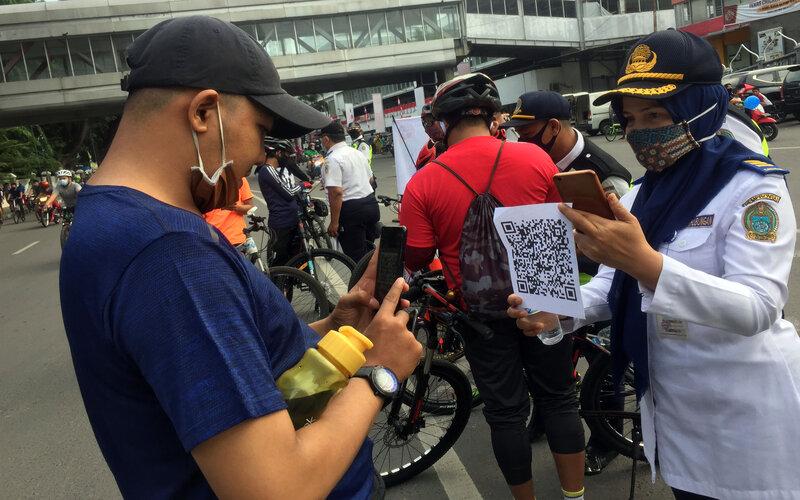 Sejumlah warga memindai kode batang (QR barcode) tentang imbauan yang diberikan petugas Dinas Perhubungan Sumut saat menyosialisasikan panduan gowes atau bersepeda aman di kawasan Lapangan Merdeka Medan, Sumatera Utara, Minggu (26/7/2020). Panduan tersebut bertujuan mengingatkan warga untuk bersepeda yang aman sesuai dengan protokol kesehatan dalam adaptasi kebiasaan baru di masa pandemi Covid-19. - Antara/ Septianda Perdana