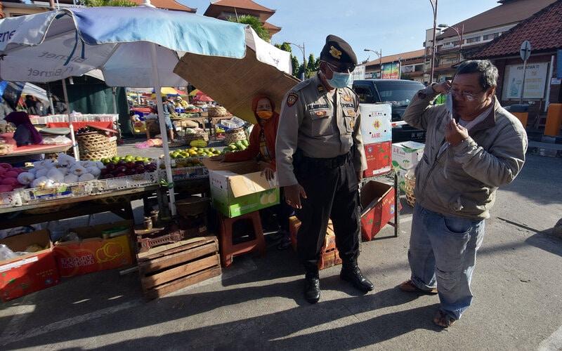 Polisi menegur warga yang tidak menggunakan masker dalam Operasi Aman Nusa II tahap 4 di Pasar Badung, Denpasar, Bali, Selasa (28/7/2020). Kegiatan tersebut untuk meningkatkan kedisiplinan penerapan protokol kesehatan karena kasus penularan COVID-19 secara transmisi lokal di Bali masih bertambah pada masa adaptasi kebiasaan baru. - Antara/Nyoman Hendra Wibowo