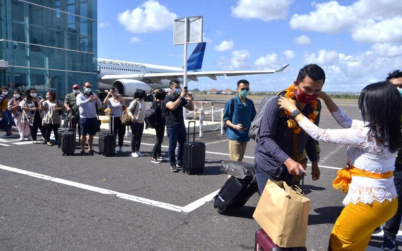 Petugas mengalungkan bunga untuk menyambut penumpang pesawat rute domestik yang tiba di Bandara Internasional I Gusti Ngurah Rai, Badung, Bali, Jumat (31/7/2020). Pemprov Bali mulai membuka sektor pariwisata bagi wisatawan domestik pada Jumat (31/7) dengan sejumlah persyaratan yang mengedepankan aspek kesehatan dan kualitas untuk memberi pelindungan, kenyamanan dan keamanan bagi wisatawan yang berkunjung selama masa pandemi Covid-19. - Antara/Fikri Yusuf