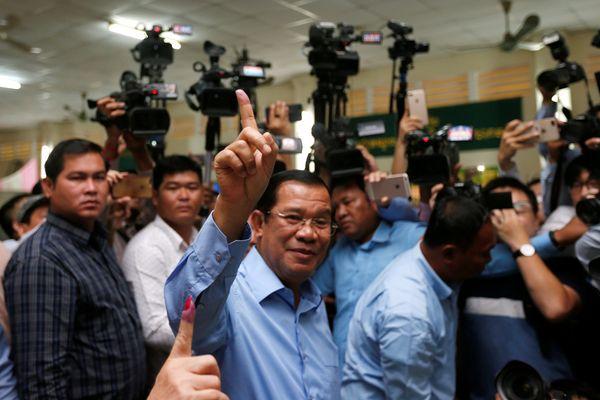 Perdana Menteri (PM) Kamboja Hun Sen, yang juga Presiden Cambodian People's Party (CPP), (tengah) menunjukkan jarinya setelah memilih dalam Pemilu di Takhmao, Provinsi Kandal, Kamboja, Minggu (29/7). - Reuters/Samrang Pring