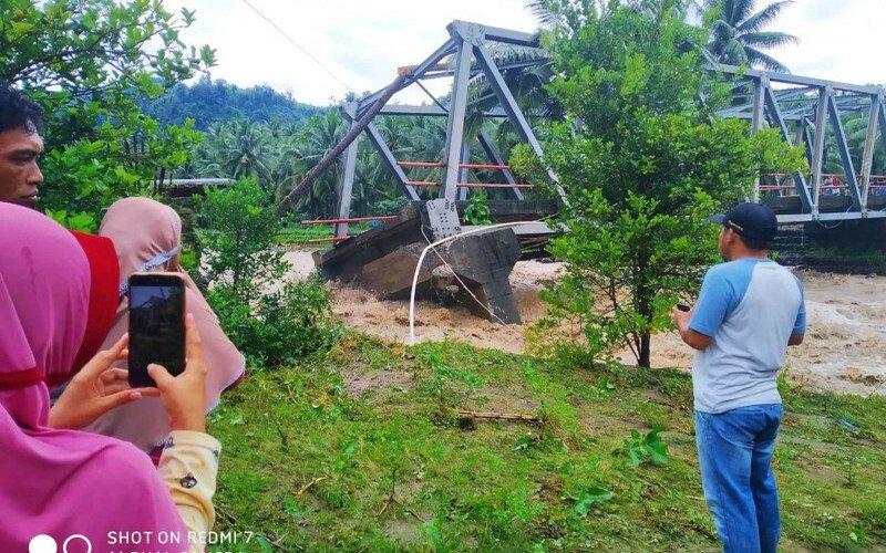 Banjir bandang di Kabupaten Bolaang Mongondow Selatan, Sulut menyebabkan salah satu jembatan di daerah tersebut ambruk. - Antara/BNPB