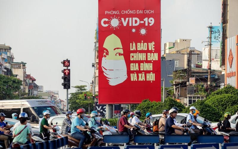 Papan iklan besar berisi pemberitahuan tentang virus corona terpampang di jalanan Hanoi, Vietnam, Jumat (29/5/2020). - Bloomberg/Maika Elan